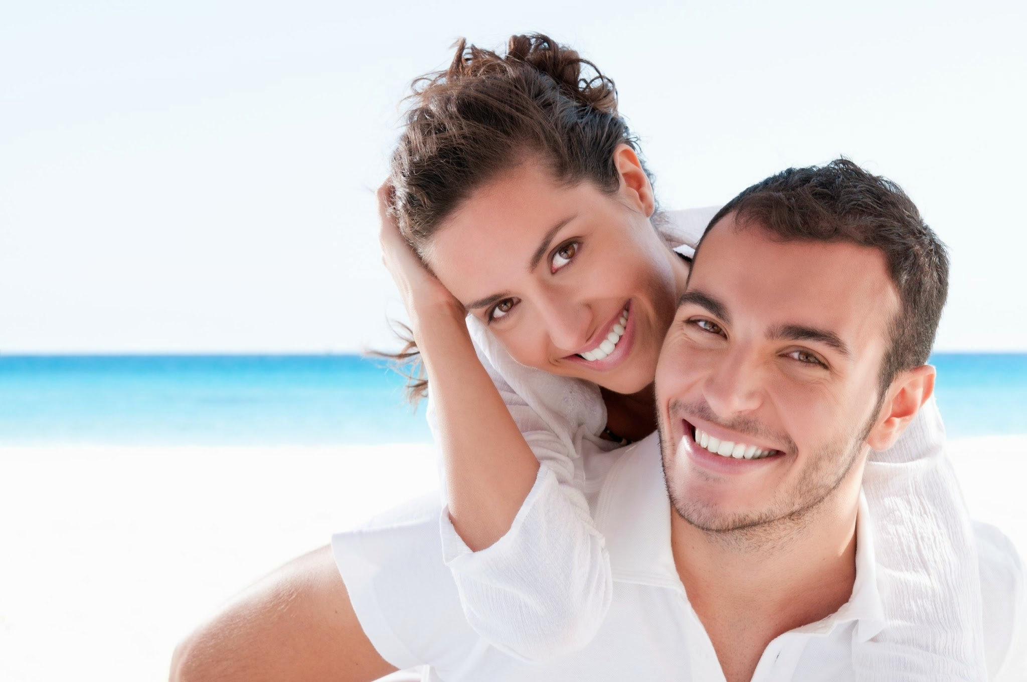 Young couple smiling and showing off how restorative dentistry services keeps their smiles looking their best.