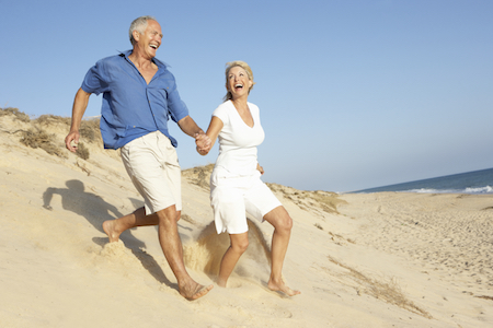 Older couple having fun at the beach feeling confident with good fitting dentures which are a restorative dentistry treatment.